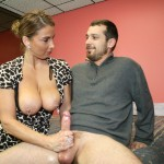 Stacie Starr gives a handjob to a young man with her big tits out